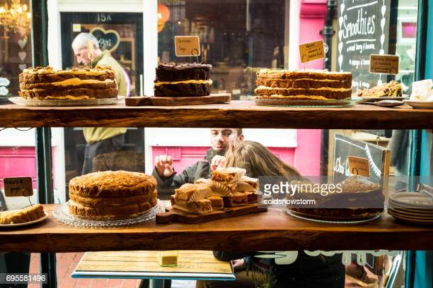 Freshly baked cakes on display in bakery window, Brighton, UK