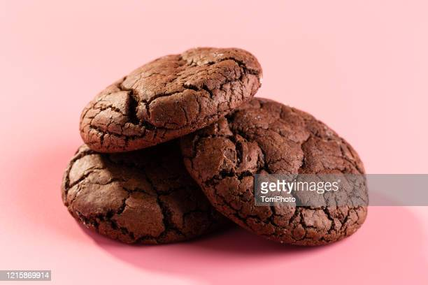 freshly baked chunky chocolate cookies on pink background - cookie stock pictures, royalty-free photos & images