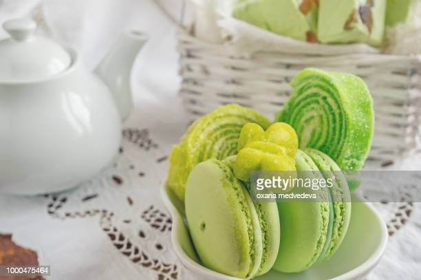 Freshly baked colored macaroons in wicker basket with handles with small white flowers on wooden...