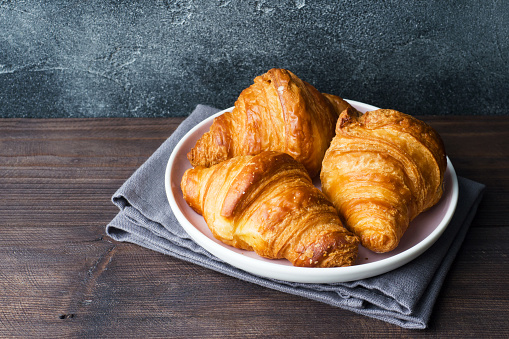 Freshly baked croissants on a plate, dark background, copy space. 1069479148