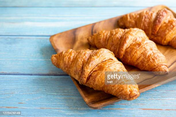 freshly baked croissants on wooden background - バンズ ストックフォトと画像