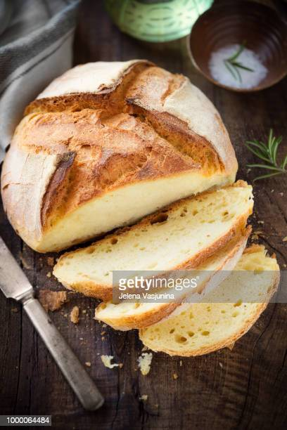 Freshly baked homemade bread on dark rustic wooden table with salt and olive oil at the background