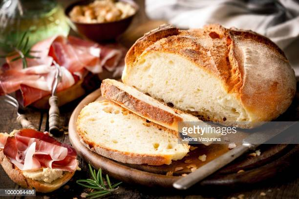Freshly baked loaf of rustic homemade bread served with prosciutto ham, hummus and olive oil