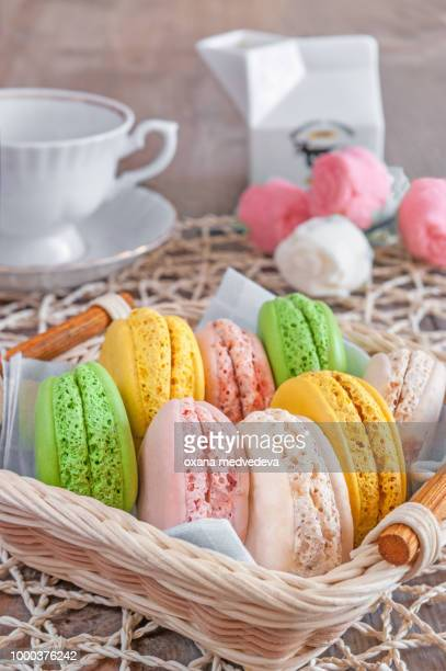 Freshly baked macarons in a wicker basket with marshmallows and a Cup of tea.