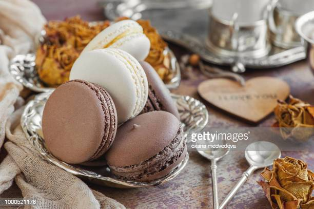 Freshly baked macaroons on a metal plate with small flowers and a wooden heart . Selective focus.