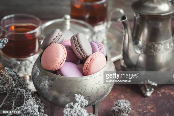 Freshly baked macaroons on metal plate with small white flowers and tea appliances composition on...