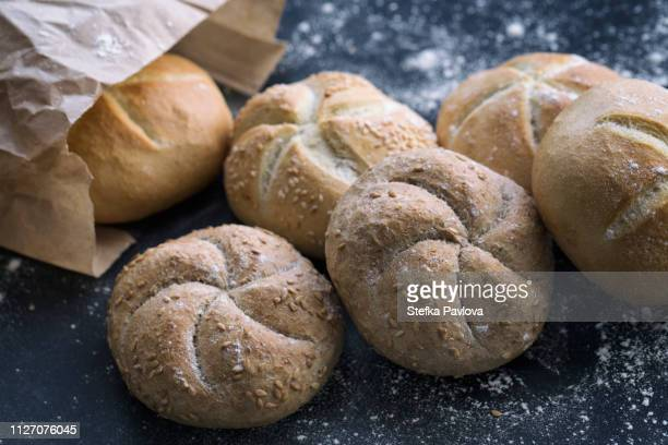 freshly baked mixed bread rolls in a paper bag - gluten free bread stock pictures, royalty-free photos & images