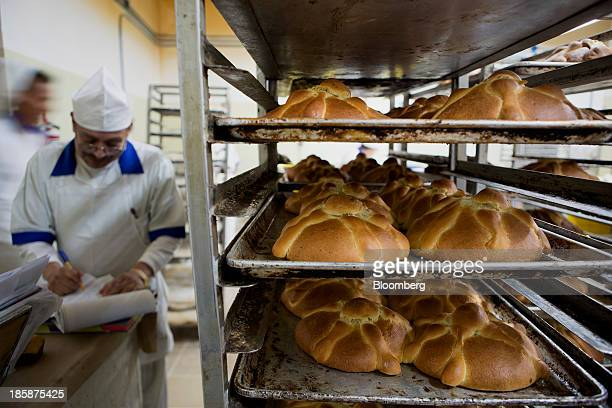 Freshly baked pan de muerto sits on racks at La Ideal bakery in Mexico City Mexico on Thursday Oct 24 2013 The pan de muerto or bread of the dead is...