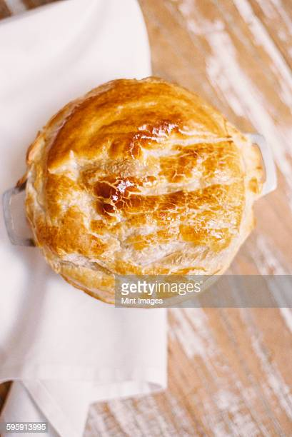 A freshly baked pie with a pastry top on a table