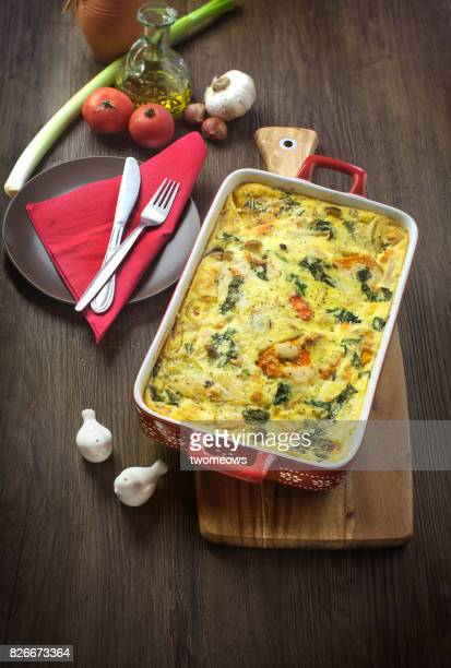 Freshly baked quiche on wooden table top.