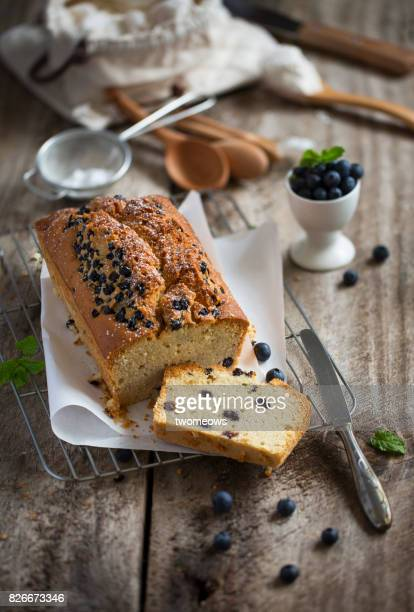 Freshly baked sliced blueberry cake loaf on rustic wooden kitchen counter table top.