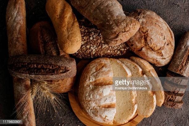 freshly baked traditional bread on wooden table - bread stock pictures, royalty-free photos & images