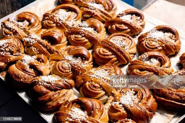 freshly baked traditional swedish cinnamon buns (kanelbullar) - sweet bun stock pictures, royalty-free photos & images