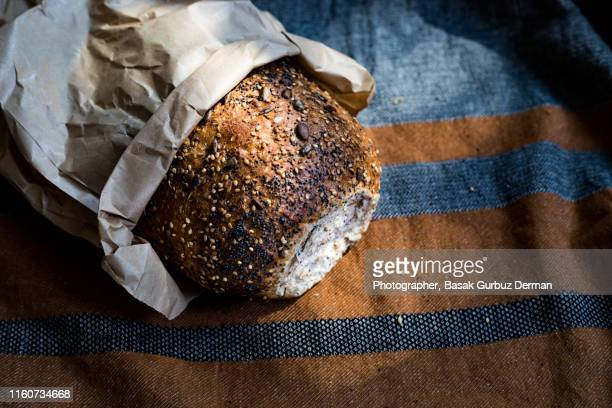 freshly baked whole wheat and wholegrain organic bread in paper bag on linen tablecloth - basak gurbuz derman stock photos and pictures