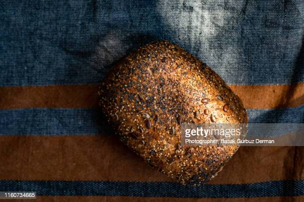 freshly baked whole wheat and wholegrain organic bread on linen tablecloth - basak gurbuz derman stock photos and pictures