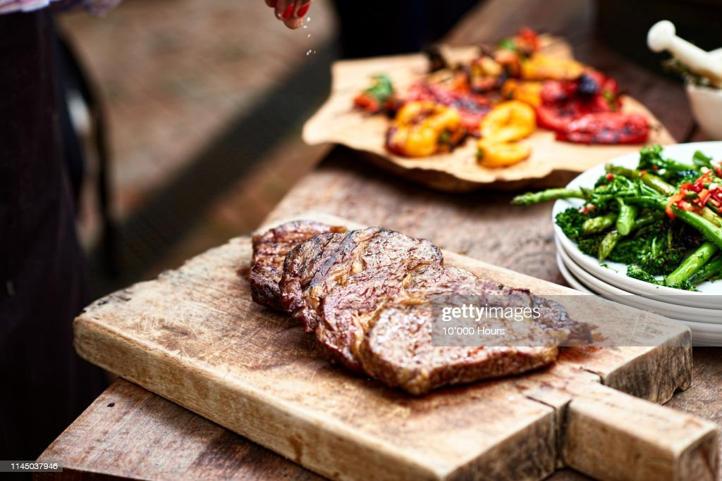 Freshly cooked steak on wooden board with salt flakes : Stockfoto