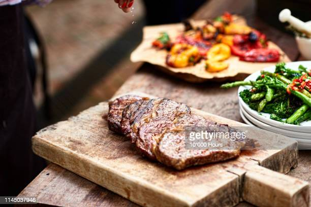 freshly cooked steak on wooden board with salt flakes - grelhado cozido - fotografias e filmes do acervo