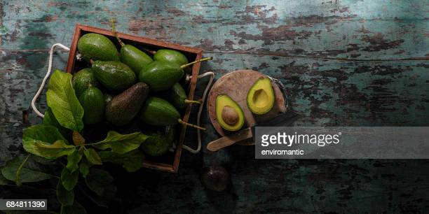 Freshly cut in half advocado on a cutting board with a knife, on an old turquoise coloured table next to a wooden crate with fresh ripe and unripe advocados and some advocado leaves.