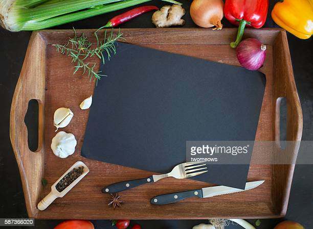 Freshly cut vegetables and cooking utensils on text space wooden chopping board.