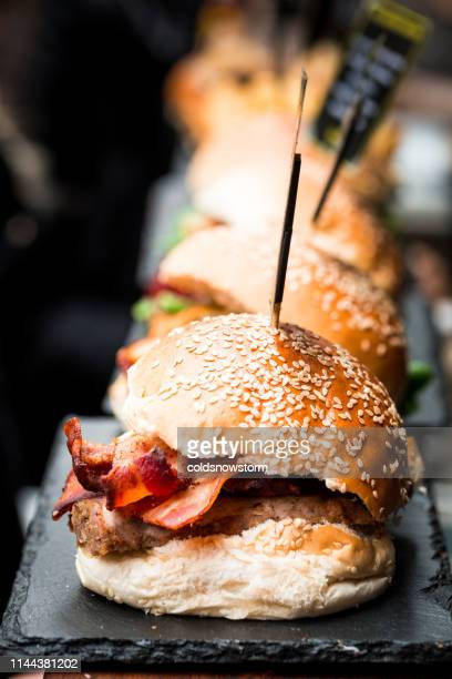 freshly flame grilled bacon cheese burgers in a row - bun stock pictures, royalty-free photos & images