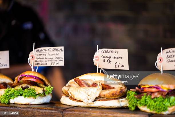 Freshly flame grilled burgers displayed in a row at Borough Market, London