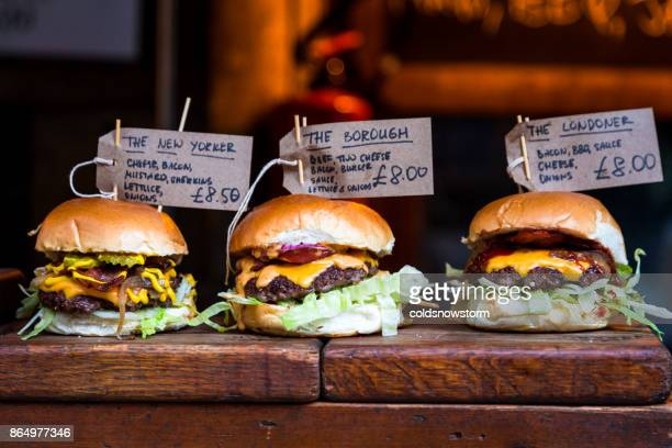freshly flame grilled burgers displayed in a row at borough market, london - borough market stock pictures, royalty-free photos & images