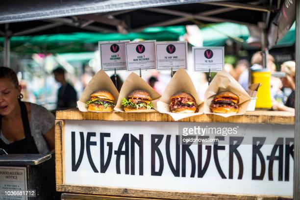 freshly flame grilled vegan burgers displayed in a row - borough market stock pictures, royalty-free photos & images