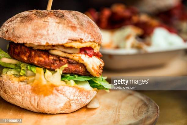freshly flame grilled vegetarian halloumi cheeseburger on wooden counter at food market - meat substitute stock pictures, royalty-free photos & images