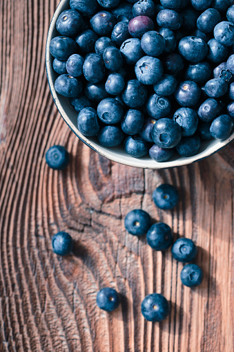 Freshly gathered blueberries put into ceramic bowl. Some fruits freely scattered on old wooden table. Shot from above 949476670