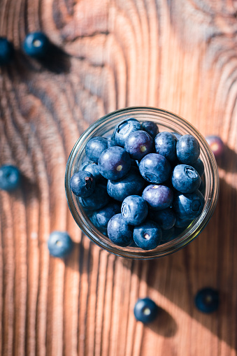 Freshly gathered blueberries put into jar. Some fruits freely  scattered on old wooden table. Shot from above 949476466