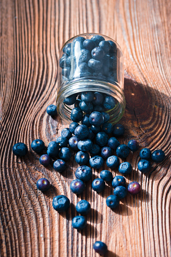 Freshly gathered blueberries put into jar. Some fruits freely scattered on old wooden table. Shot from above 949503940
