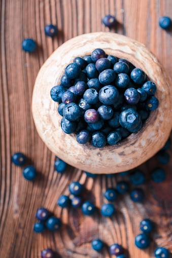 Freshly gathered blueberries put into old ceramic bowl. Some fruits freely scattered on old wooden table. Shot from above 949476414