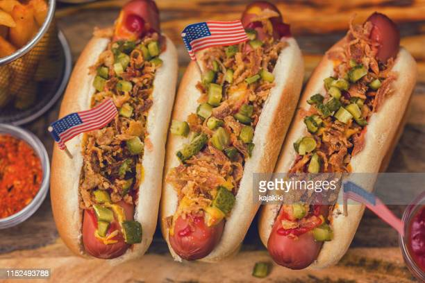 freshly grilled hot dogs with pickles and dried onions for the 4th of july - american culture stock pictures, royalty-free photos & images