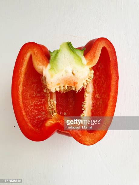 freshly half cut capsicum against white background - red bell pepper stock pictures, royalty-free photos & images