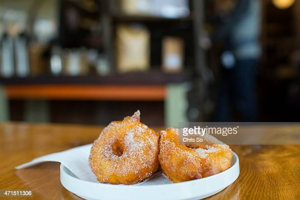 Freshly made apple fritters dusted with cinnamon and sugar Michele Henry samples The Purple Penguin's apple fritters for Sourced