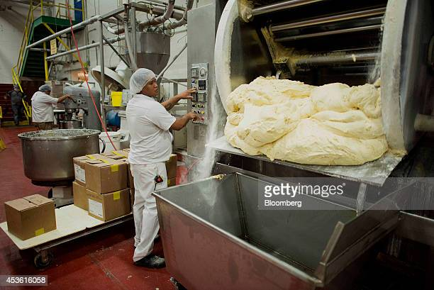 Freshly made dough comes out of a mixer in the production area at the Orlando Baking Co in Cleveland Ohio US on Wednesday Aug 13 2014 Wheat rose...