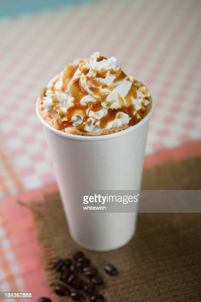 A freshly made latte with caramel sauce drizzled over cream