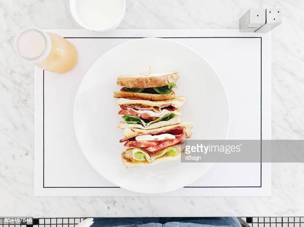 Freshly made organic bacon, lettuce and tomato sandwich served on plate with fresh fruit juice