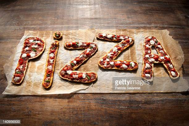 freshly made pizza spelling out the word 'pizza' - font stock-fotos und bilder