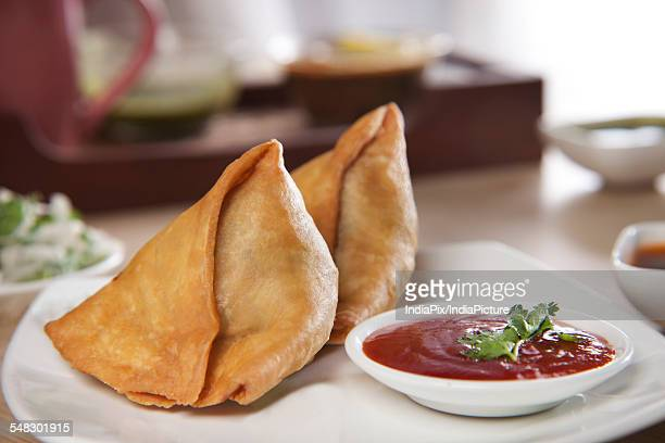 freshly made samosas with sauce on plate - savoury food stock photos and pictures