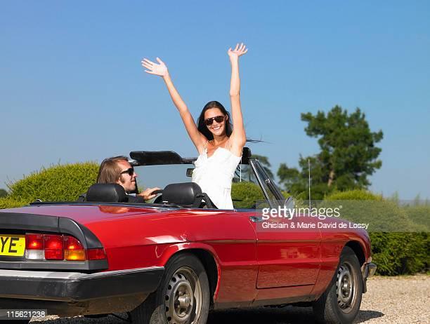 Freshly married couple in car, goodbye
