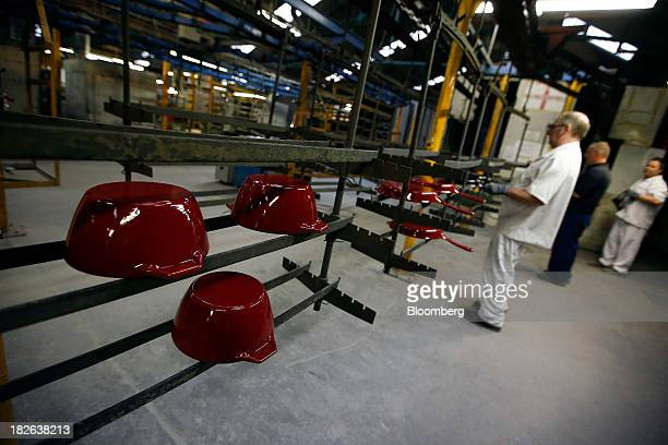Freshly painted maroon cast iron AGA casserole dishes and frying pans produced by AGA Rangemaster Plc move along the production line during the...