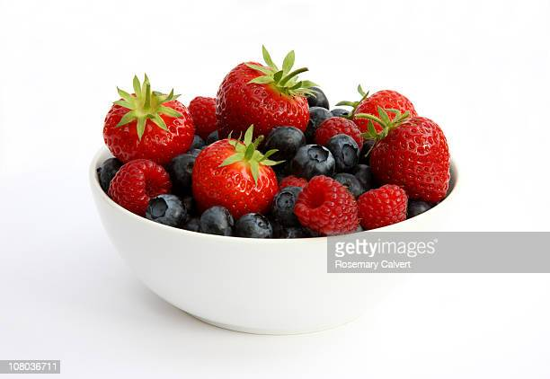 freshly picked berries in white bowl. - berry fruit stock pictures, royalty-free photos & images
