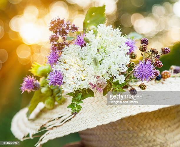 freshly picked wildflowers with hazelnut and blackberry plants in straw hat - mazzi fiori di campo foto e immagini stock