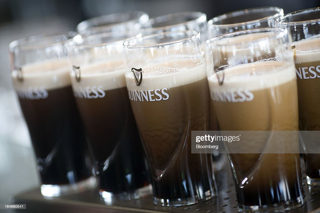 Freshly poured Guinness settles in branded pint glasses on the bar in the Guinness Gravity Bar at the St. James's Gate Brewery, in Dublin, Ireland, on Saturday, March 16, 2013. Ireland's renewed competiveness makes it a beacon for the U.S. companies such as EBay, Google Inc. and Facebook Inc., which have expanded their operations in the country over the past two years. Photographer: Simon Dawson/Bloomberg via Getty Images