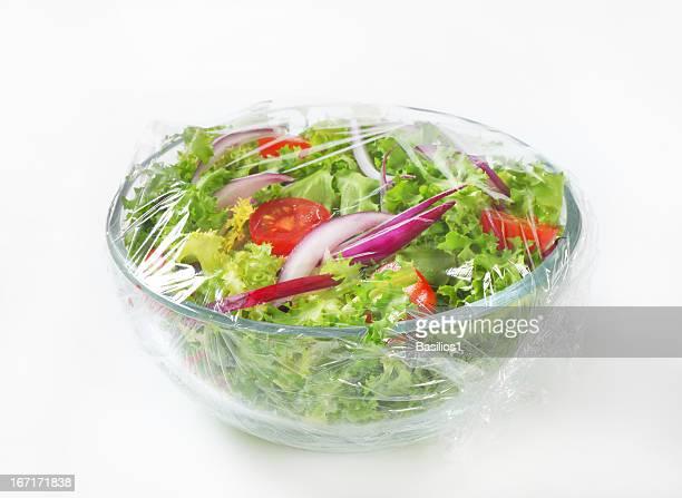 Freshly prepared vegetable salad covered in plastic wrap