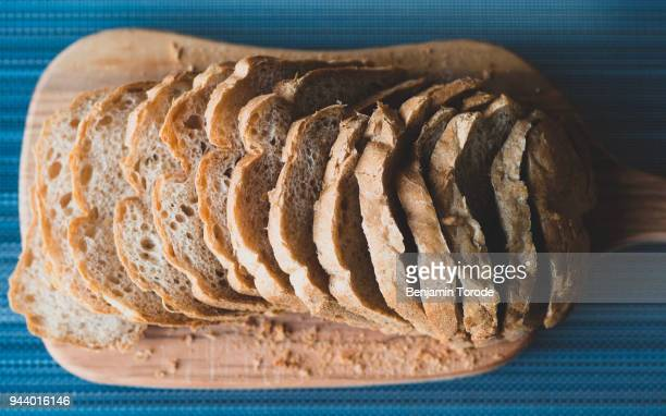 freshly sliced whole wheat bread on cutting board - whole wheat stock pictures, royalty-free photos & images