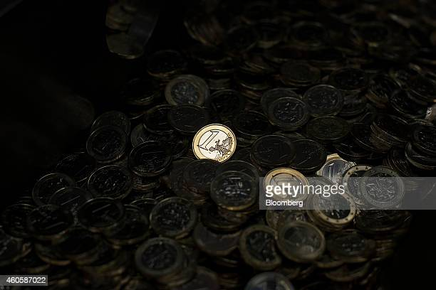 Freshly struck new Lithuanian one euro coins sit after minting in the Bank of Lithuania mint in Vilnius Lithuania on Tuesday Dec 16 2014 Lithuania...