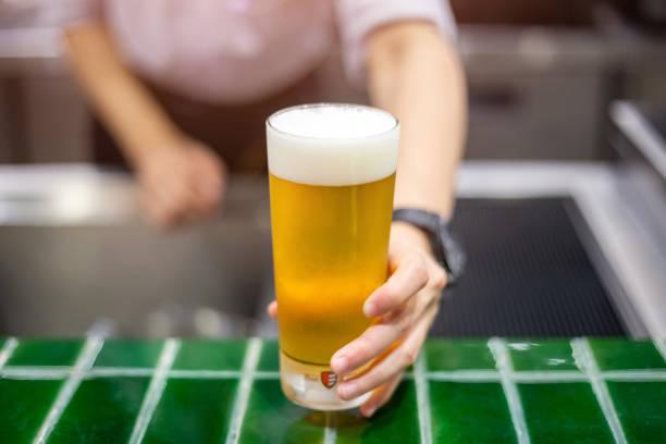 Freshly tapped beer. Bartender holding a freshly tapped glass