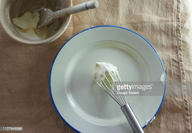 freshly whipped cream at home with whisk and wooden spoon in mixing bowl. - wire whisk stock pictures, royalty-free photos & images